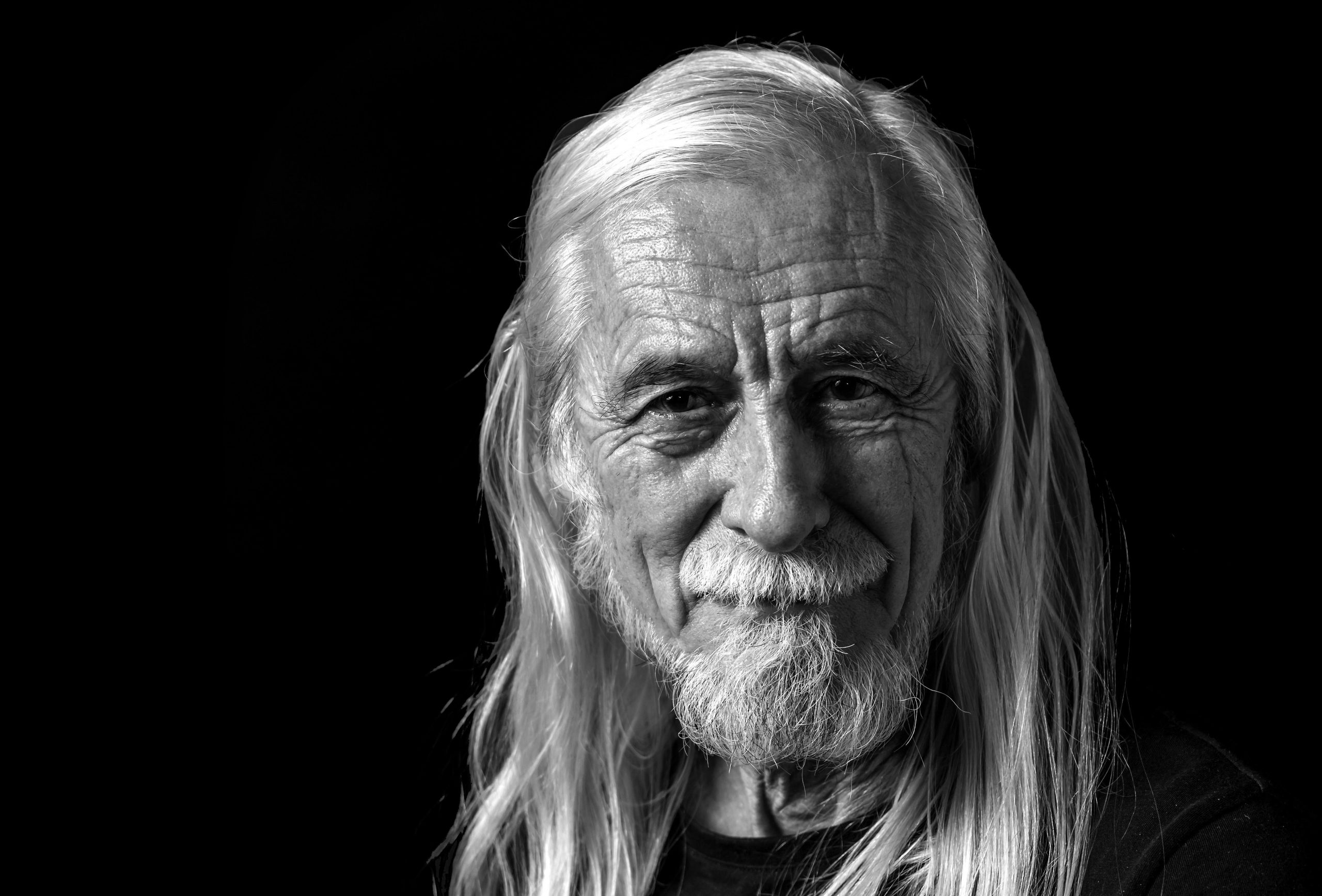Low key portrait of attractive long gray hair old man looking at camera with tranquility.